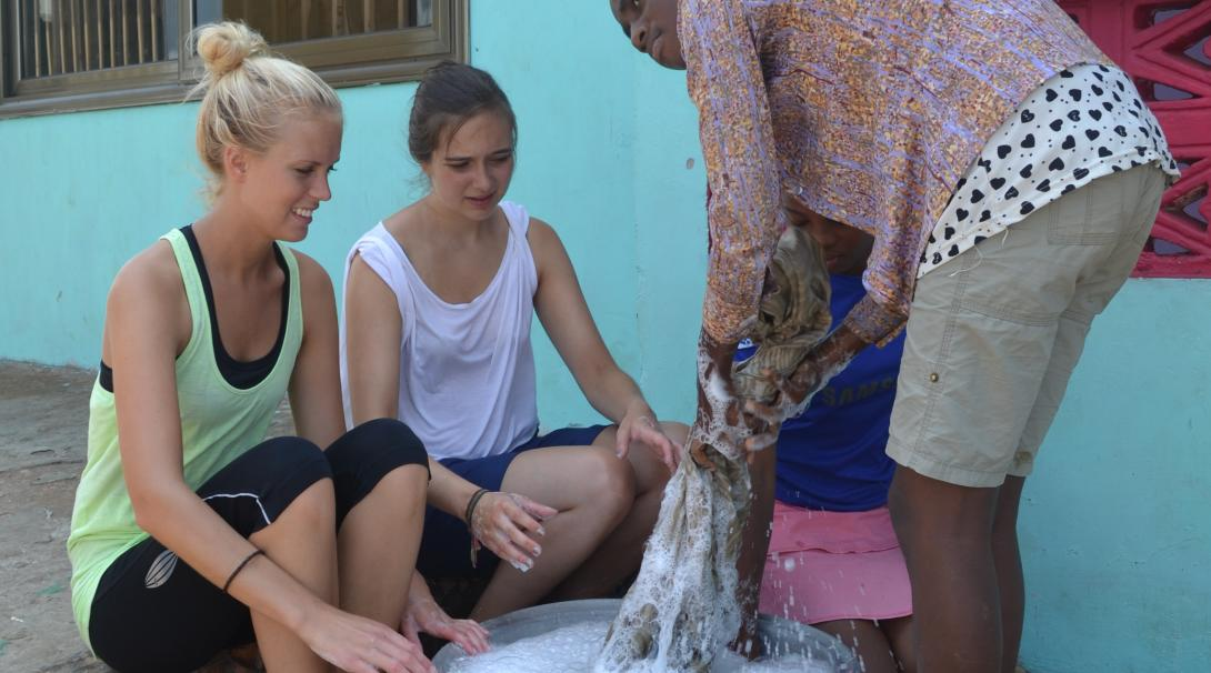 Projects Abroad volunteers get a handwashing activity ready during their childcare volunteer work in Ghana